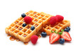 canvas print picture - Yummy waffles with berries and caramel syrup on white background
