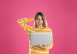 canvas print picture - Portrait of surprised young woman in casual outfit with laptop on color background