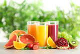 Three glasses with different juices and fresh fruits on table against blurred background