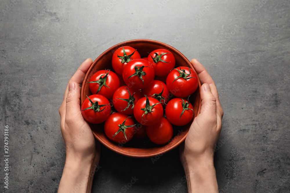 Fototapety, obrazy: Woman holding wooden bowl with ripe cherry tomatoes at table, above view