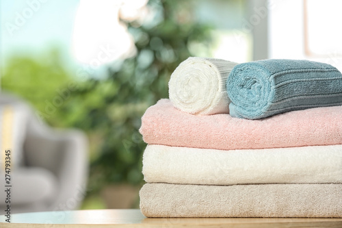 Fotografia Clean soft terry towels on table indoors, closeup. Space for text