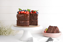 Stand With Tasty Chocolate Cake On White Table