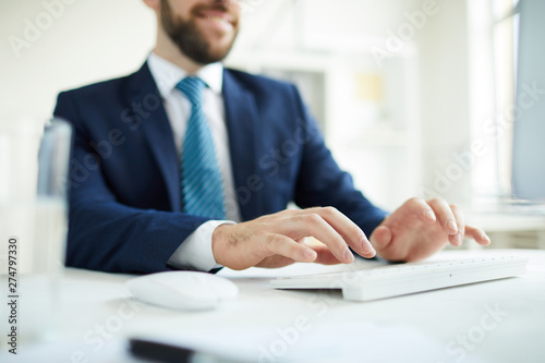 Fototapety, obrazy: Close-up of busy male manager sitting at desk and typing on computer keyboard while preparing report for annual meeting
