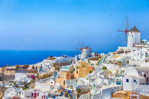 Poster Light pink Travel Destinations. Picturesque Cityscape of Oia Village in Santorini Island Located on Volcanic Calderra at Daytime. Traditional Windmills on Background.