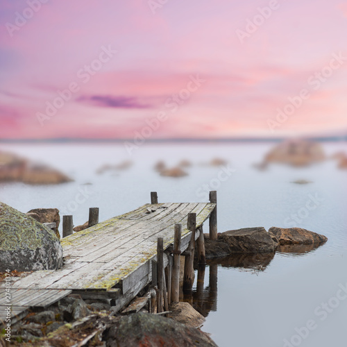 Photo Old wooden jetty in calm lake at purple sunset