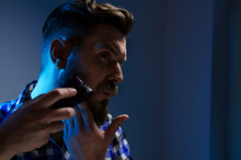 Studio Shot, Closeup Of Man Shaving Beard With Electric Shaver , Dark Background