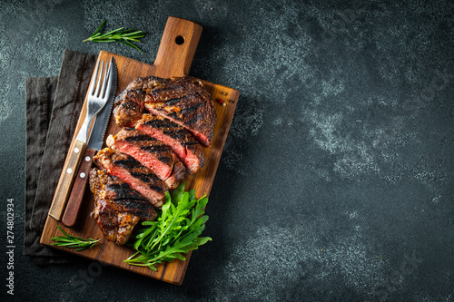 Sliced steak ribeye, grilled with pepper, garlic, salt and thyme served on a wooden cutting Board on a dark stone background Fototapet