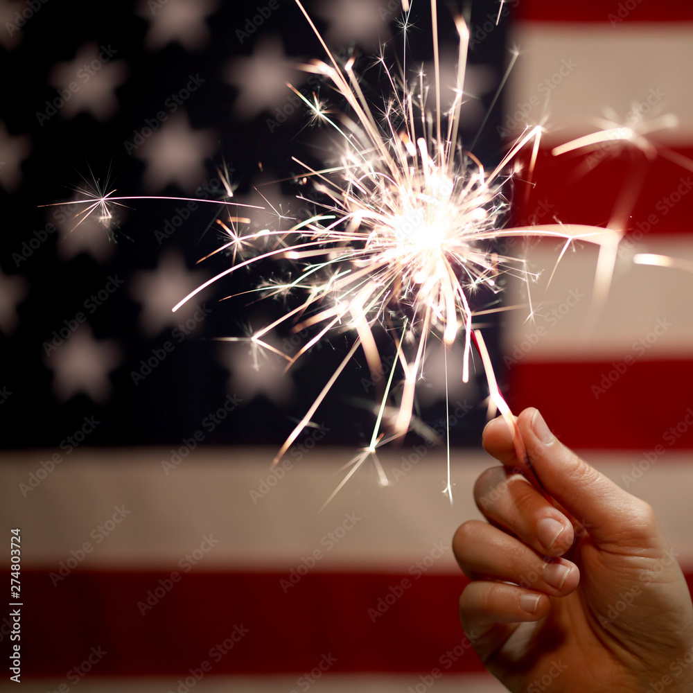 Fototapety, obrazy: Hand holding lit sparkler in front of the American Flag for 4th of July celebration