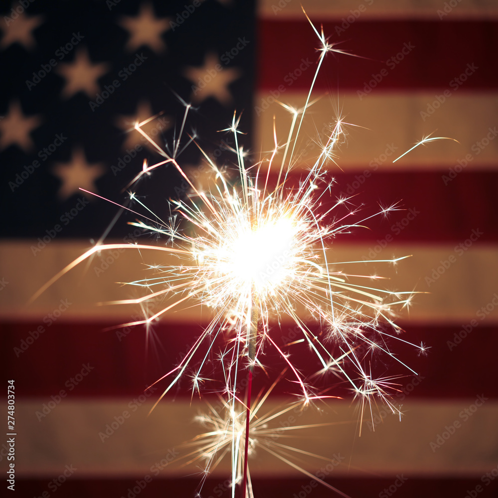 Fototapety, obrazy: Lit sparkler in front the American Flag for 4th of July celebration