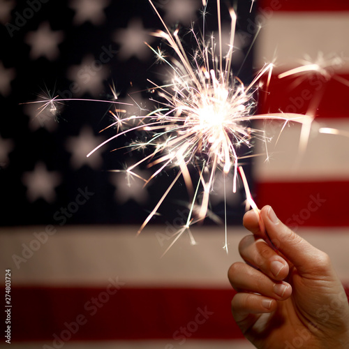 Hand holding lit sparkler in front of the American Flag for 4th of July celebration - 274803724