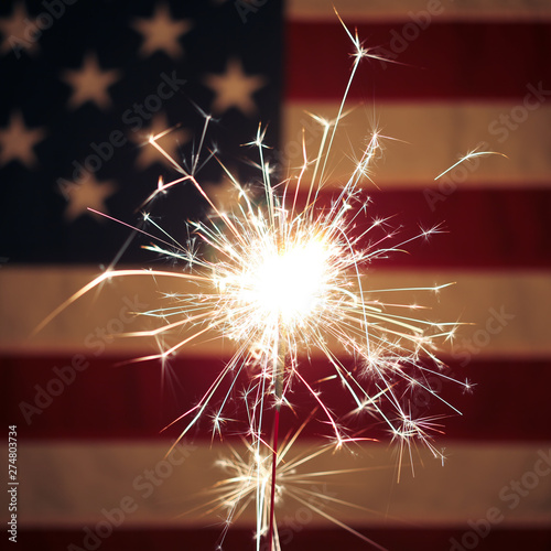 Canvas Prints Countryside Lit sparkler in front the American Flag for 4th of July celebration