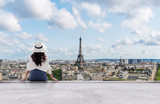 Fototapeta Fototapety Paryż - Young traveler woman in white hat looking at Eiffel tower, famous landmark and travel destination in Paris, France in summer