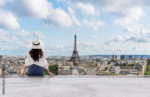 Poster Paris Young traveler woman in white hat looking at Eiffel tower, famous landmark and travel destination in Paris, France in summer