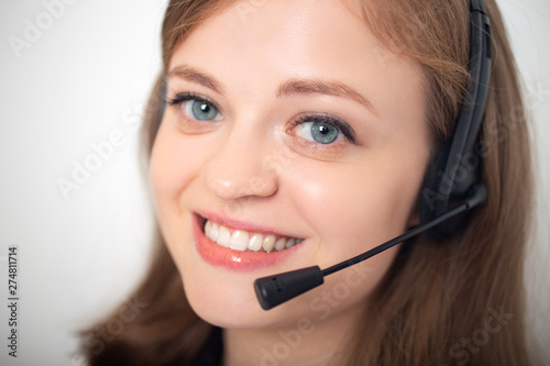 Fotografie, Obraz Happy smiling young caucasian woman with headset phone in a call center or offic