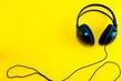 Leinwanddruck Bild - Top view of black headphone against yellow isolated background. Listening music theme.