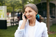 canvas print picture - Elegant attractive mature businesswoman wearing white jacket and headscarf in her gathered hair smiling while speaking on mobile phone outdoors. Trendy looking senior female using electronic gadget
