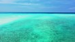 Aerial view, low flight over shallow turquoise water next to a sandbank. In Jamaica. Dolly in