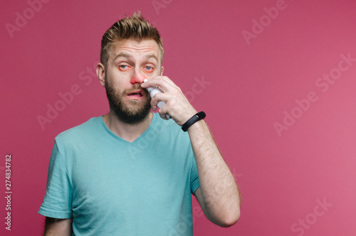 Fototapeta  studio picture from a young man uses nose spray