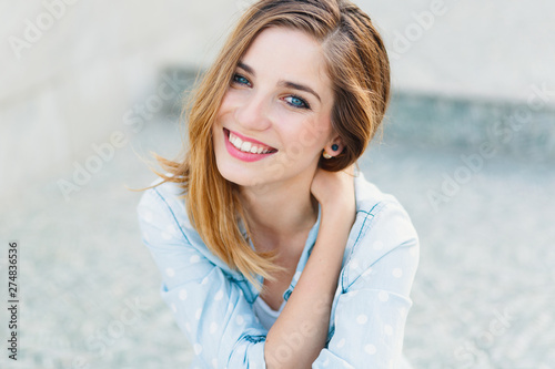 Happy young Caucasian woman demonstrating perfect teeth over light gray blurred background