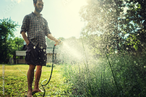 Canvastavla Hipster young man watering plants in a country house, summer and garden care
