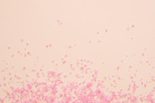 Spa Therapy. Pink Bath Salt Crystals Scattered Over Peach Surface. Abstract Background. Copy Space.