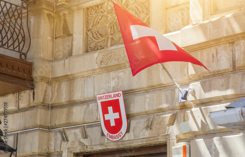 Valokuva  Switzerland national flags flying in the wind by a building in a city, square re
