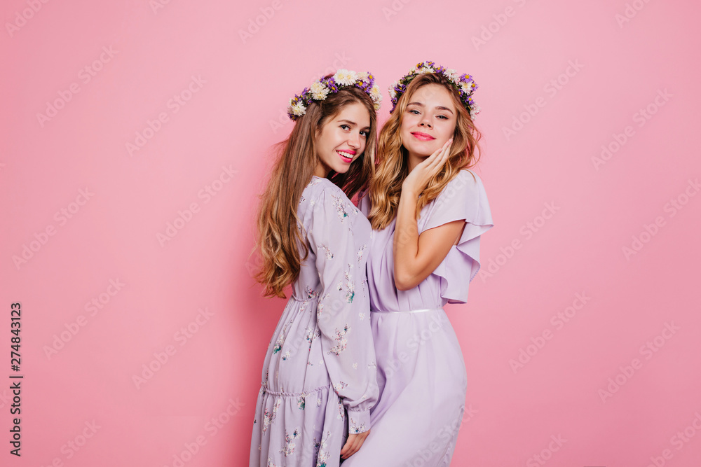 Fototapety, obrazy: Refined girl with blonde wavy hair posing with sister on pink background. Pleased long-haired female model in flower wreath standing beside best friend.