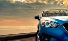 Blue Compact SUV Car With Sport And Modern Design Parked On Concrete Road By The Sea At Sunset In The Evening. Hybrid And Electric Car Technology Concept. Car Parking Space. Automotive Industry.
