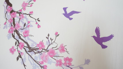 Graffiti on the wall in the form of a branch of Sakura and blue birds