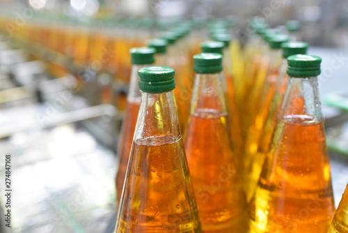 Fotomural befüllen von Glasflaschen auf dem Fliessband mit Apfelsaft in der industriellen