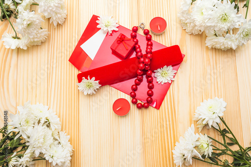 Romantic gift concept. Valentines day or 8th march or love holiday. Letter, case and flowers. Table setting on wooden background, top view
