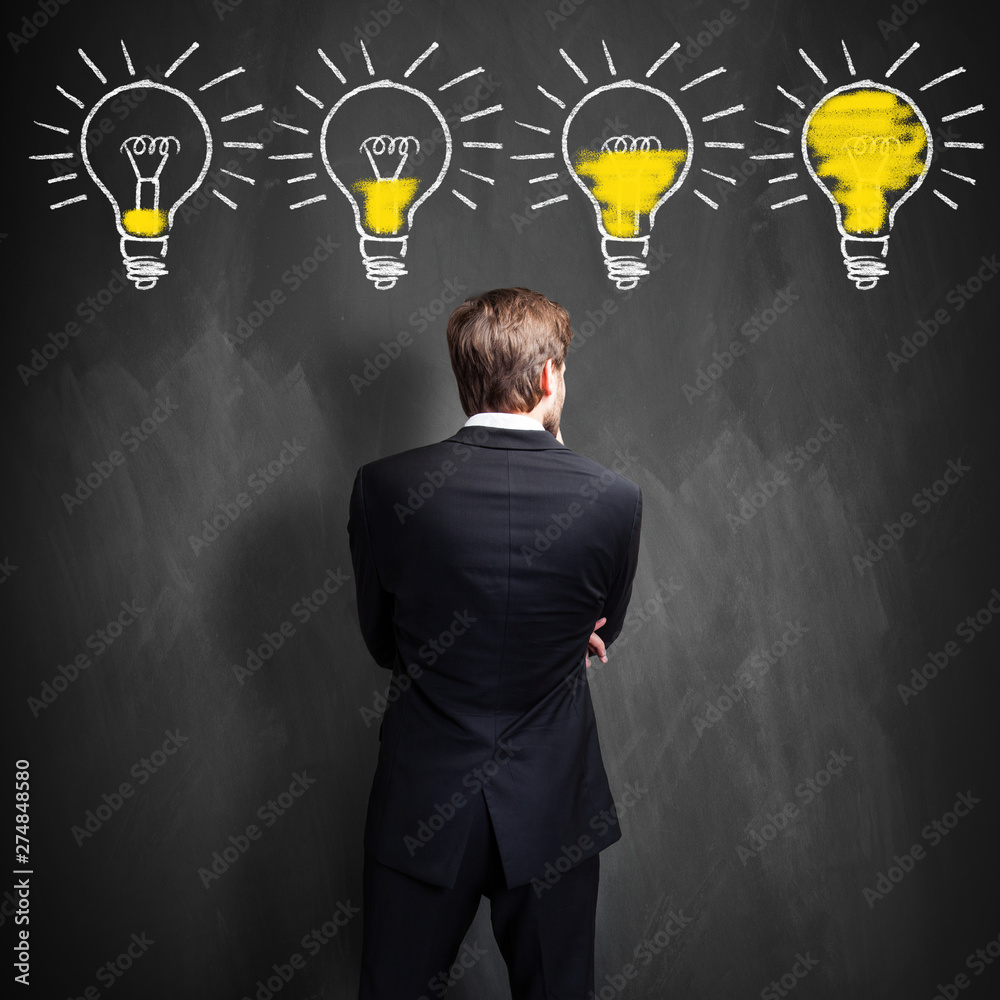 Fototapety, obrazy: successful businessman standing in front of a blackboard with lightbulbs, symbolizing having an idea in development
