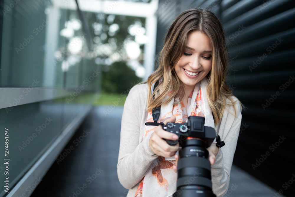 Fototapety, obrazy: Woman is a professional photographer with dslr camera