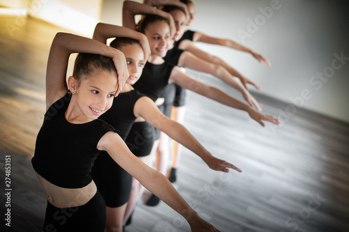 In de dag Dance School Group of fit happy children exercising dancing and ballet in studio together