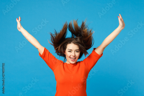Valokuvatapetti Beautiful fun young woman wearing red orange dress fooling around fluttering flying hair raised hands up isolated over trendy blue wall background
