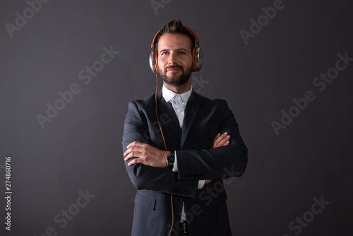 A smiling young businessman listening to music - 274860716