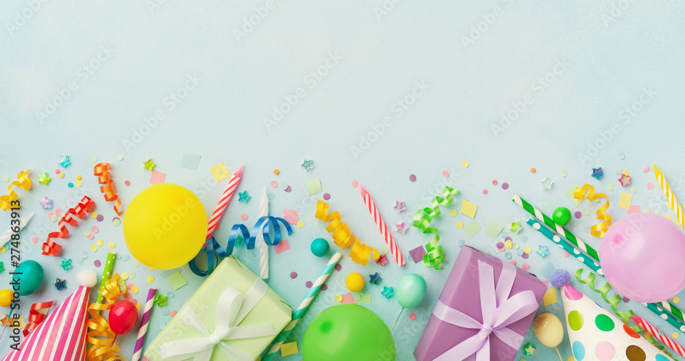 Fototapety, obrazy: Holiday background with balloons, gift boxes and confetti. Birthday and party supplies on blue table top view. Banner format.