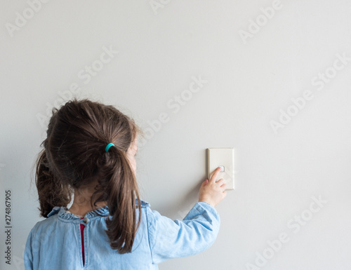 Papel de parede Rear view of little girl turning off Australian light switch on neutral wall bac