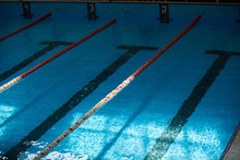 Water Surface In The Sports Swimming Pool. Blue Water And Swim Lane Dividers. Sports And Health Concept.