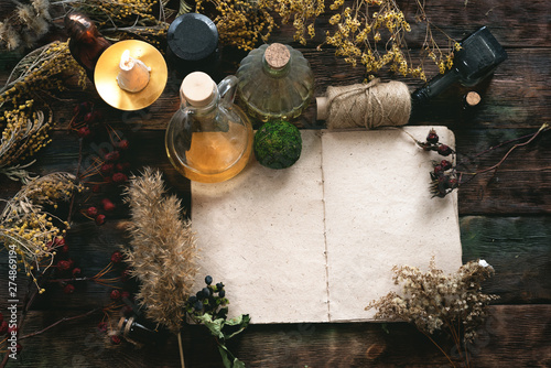 Recipe magic book and various dry herbs on a table of witch