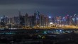 Jumeirah lake towers and Dubai marina illuminated skyscrapers and golf course during all night timelapse with blinking lights, Dubai, United Arab Emirates. Aerial view from Greens district