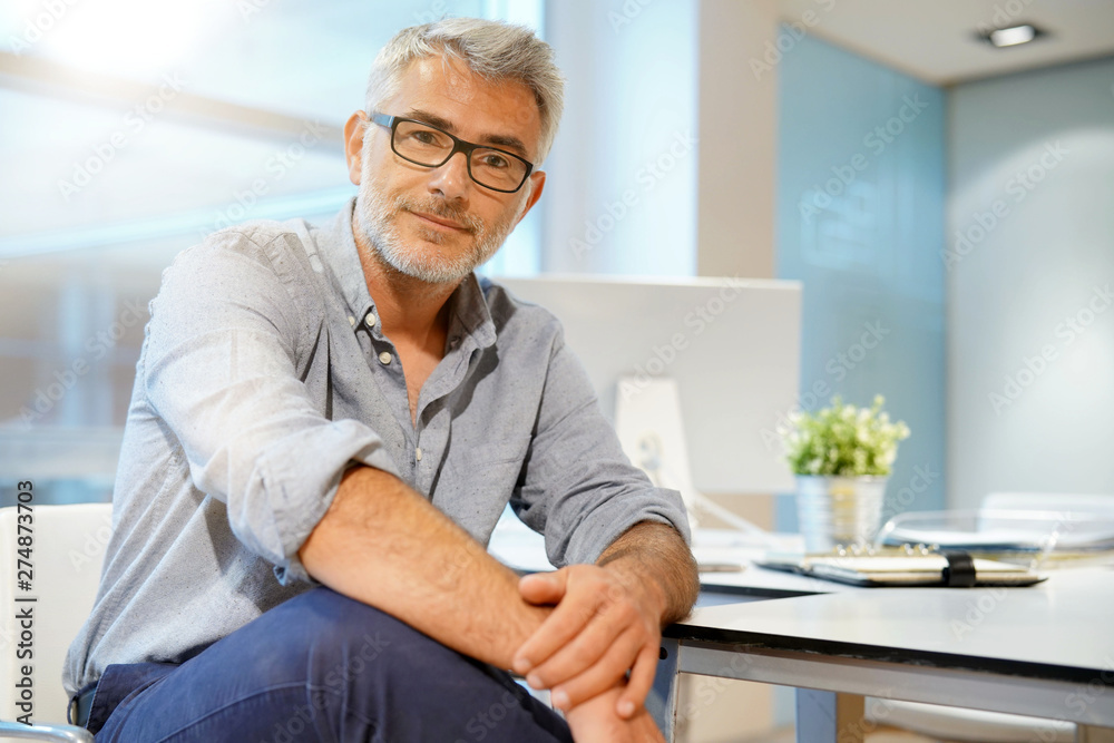 Fototapety, obrazy: Portrait of smart casual businessman looking at camera in contemporary office