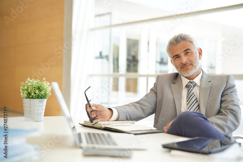 Fotografía  Mature businessman sitting casually at desk