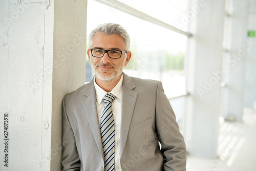 Mature businessman standing smiling at camera in office building