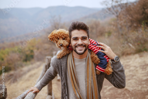 Fotomural  Handsome bearded mixed race man dressed casual walking in nature at fall and carrying his apricot poodle on shoulders