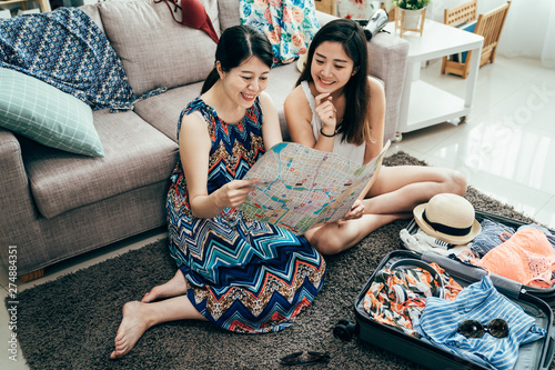 Photo  high angle top view of two happy young girl friends sitting on floor on carpet by messy suitcase
