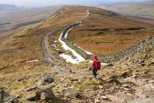 A Hiker Walking Down From The Summit Of Whernside, Part Of The Three Peaks With Sand Beds Head Pike In The Distance. The Yorkshire Dales, England.