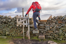 A Hiker Crossing A Stile Descending From The Summit Of Ingleborough In The Yorkshire Dales.