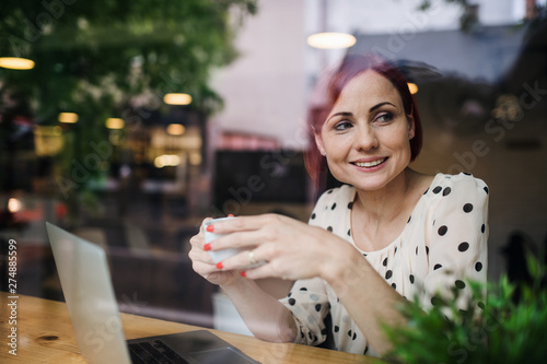 Foto auf Gartenposter Lineale Wachstum A portrait of woman with coffee sitting at the table in a cafe, shot through glass.
