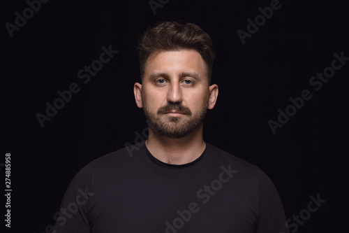 Fotografiet  Close up portrait of young caucasian man isolated on black studio background